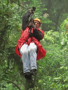 Larry Pearlman riding a zip line